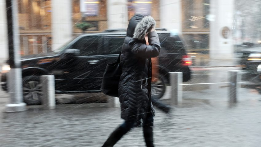 Person walks through strong wind, rain