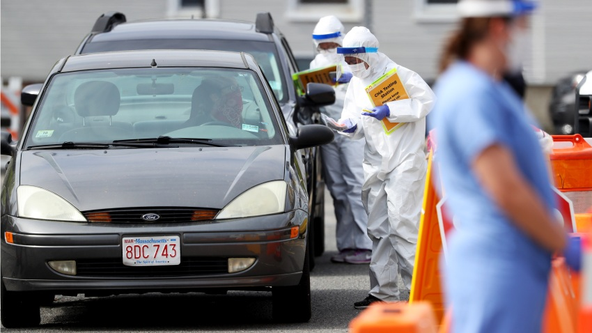 This May 15, 2020, file photo shows medical professionals at a drive-thru coronavirus testing site at CHA East Cambridge Care Center in Cambridge, Massachusetts.