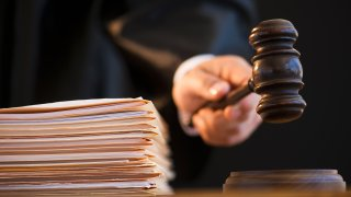 A hand holds a gavel next to a stack of manila folders.