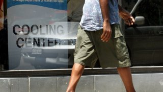 A man wearing shorts and sandals walks past a cooling center in a Chicago Department of Human Services center