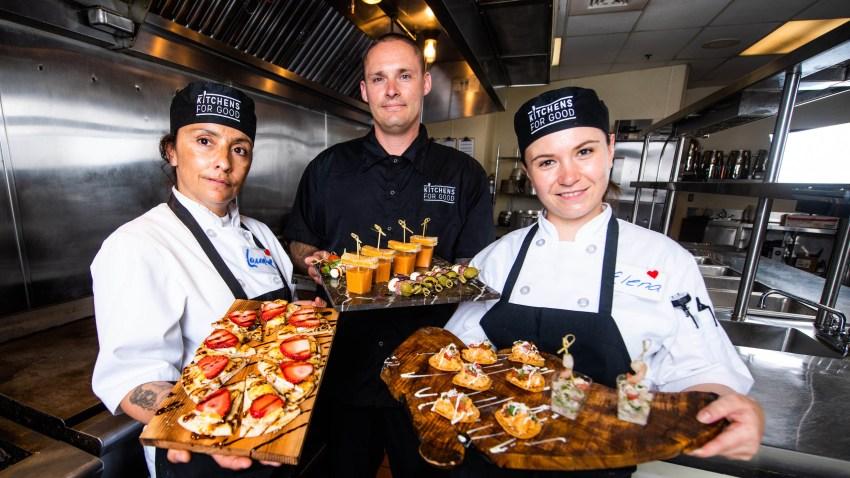 Integrantes de Kitchen for Goog sostiene bandejas de comida