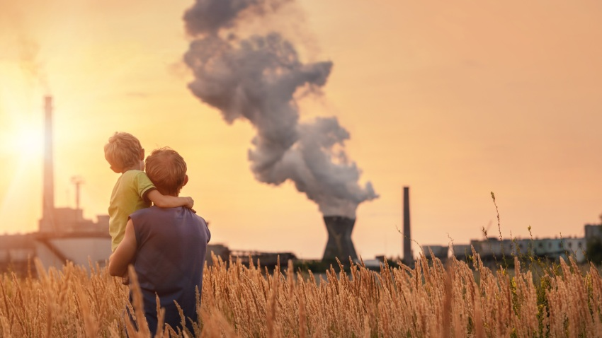 Padre carga a hijo mientras ven humo brotar de la chimenea de una fábrica.