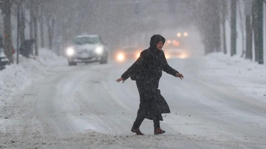 Woman walking through snowy street