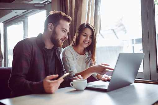 Smiling couple looks at laptop together.