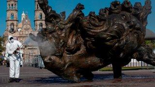 Hombre de blanco desinfecta esculturas en Zapopan