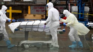 In this April 9, 2020, file photo, medical personnel move a deceased patient to a refrigerated truck serving as make shift morgues at Brooklyn Hospital Center in New York City.