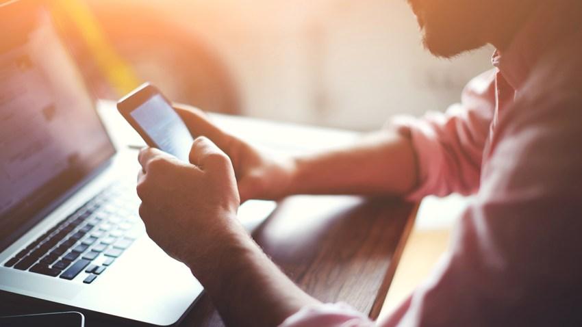 Foto genérica, persona enfrente de una computadora con un teléfono en su mano.