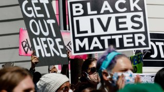 """Protesters hold banners reading """"Get Out Here"""" and """"Black Lives Matter"""" during a demonstration led by the NAACP"""