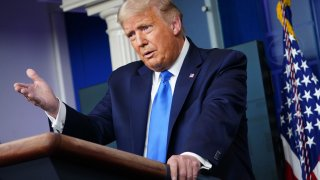 President Donald Trump speaks from a podium at the White House.