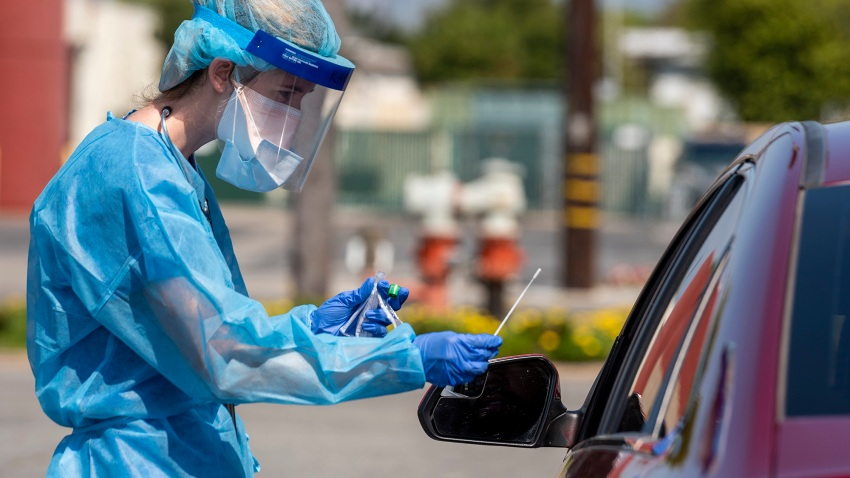 a Physician Assistant with AltaMed Health Services prepares to test a drive-through patient for COVID-19.