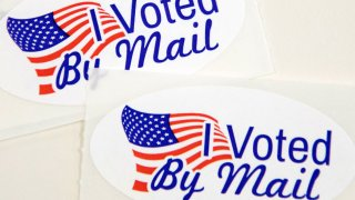 """In this Sept. 4, 2020, file photo, stickers that read """"I Voted By Mail"""" sit on a table waiting to be stuffed into envelopes by absentee ballot election workers at the Mecklenburg County Board of Elections office in Charlotte, North Carolina."""