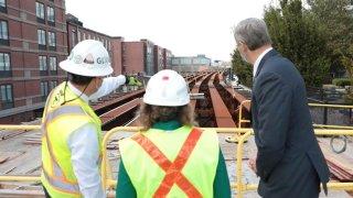 GLX Project Manager John Dalton shows Transportation Secretary and CEO Stephanie Pollack and Governor Charlie Baker GLX construction progress.