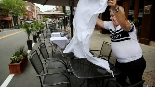 This June 11, 2020, file photo shows a server set tables on the street outside Bricco restaurant on Hanover Street in Boston's North End.