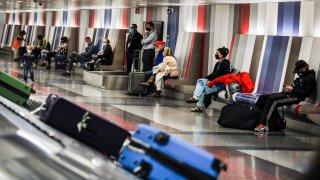 People wait for their baggage at Boston Logan International Airport in Boston