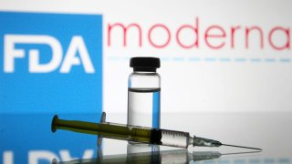 A vial and a medical syringe sit in front of an FDA sign.