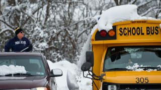 Man on back of pickup truck knocks snow off the top of a yellow school bus.