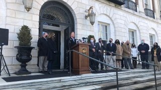 Governor Ned Lamont stands at podium outside white stone building