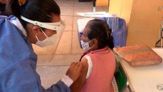 Una enfermera aplica una vacuna a mujer en Oaxaca