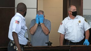 This Aug. 13, 2020, file photo shows Patrick Rose cover his face during his arraignment at Boston Municipal Court
