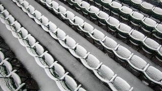 This Oct. 30, 2020, file photo shows empty seats covered in snow at Fenway Park in Boston.