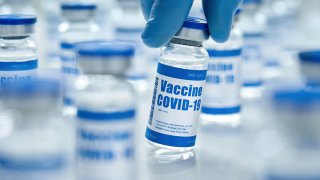 Hand with medical glove holding covid 19 corona virus vaccine vial bottle for injection on medical pharmacy background.
