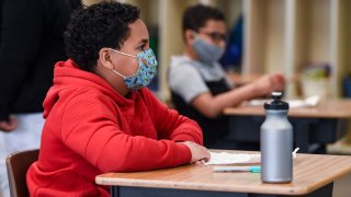 Students sit at their desks while wearing face masks.