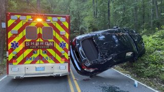 A car with a shattered back windshield wedged between a hill and an ambulance