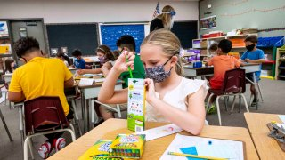 A girl puts a color pencil into its box as she wears a face mask and sits in a classroom.