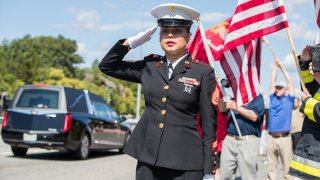 U.S. Marine SSgt. Alice Ward stands at attention on the side of I-93 North as the hearse carrying fallen Marine Sgt. Johanny Rosario Pichardo passes Stoneham on Saturday Sept. 11, 2021.