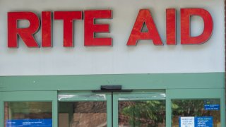 Rite Aid pharmacy sign with person walking in front