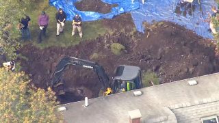An excavator digging as part of an FBI investigation in Randolph, Massachusetts, on Wednesday, Oct. 6, 2021.