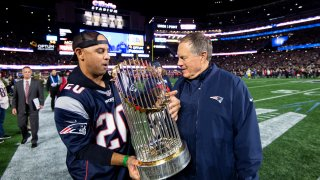 FOXBOROUGH, MA - NOVEMBER 4: This Nov. 4, 2018, file photo shows Red Sox manager Alex Cora hand the World Series trophy to head coach Bill Belichick of the New England Patriots before a game against the Green Bay Packers at Gillette Stadium in Foxboro, Massachusetts.